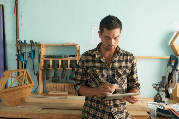 Man in casualwear checking e-mails with woodwork in the background