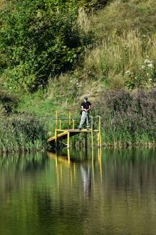 남자는 호수에서 물고기를 잡는다