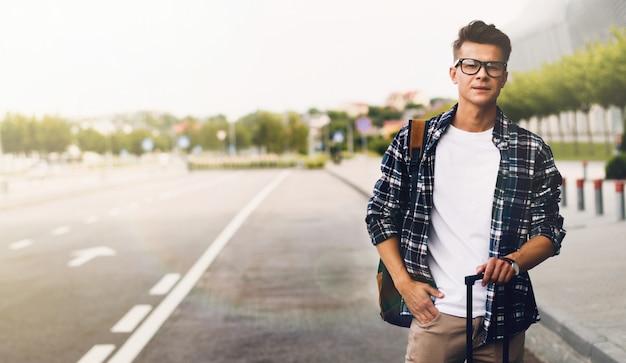 Человек ловит такси в аэропорту с чемоданом