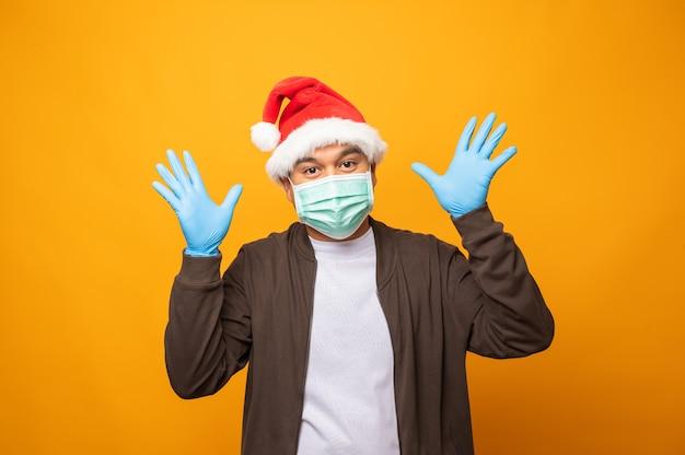 Человек празднует рождество. он одет в защитную маску и резиновые перчатки.