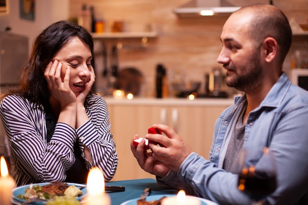Man celebrating relationship and asking girlfriend to marry him while having dinner. man asking his girlfriend to marry in the kitchen during romantic dinner. happy caucasian woman smiling being speec