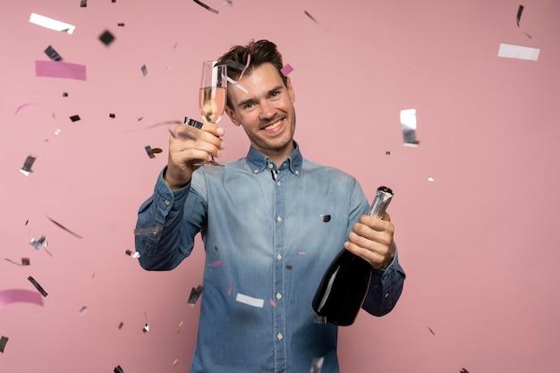Человек празднует с бутылкой шампанского и бокалом