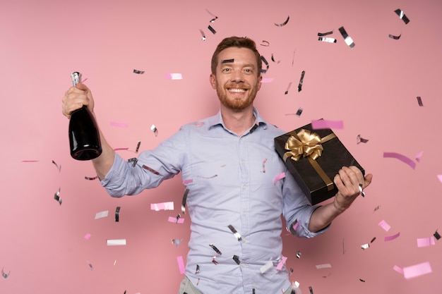 Man celebrating with champagne bottle and present