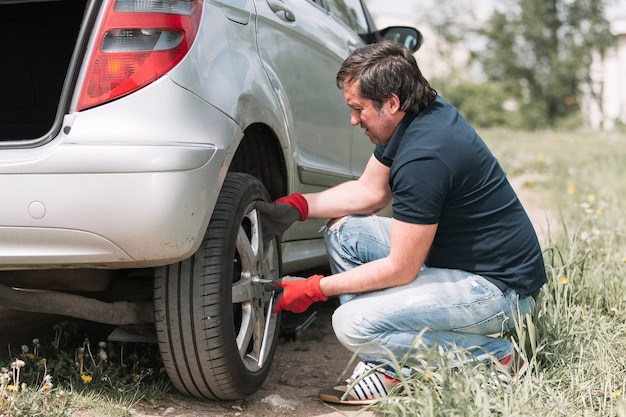 Man changes a damaged wheel while traveling . trouble on the road