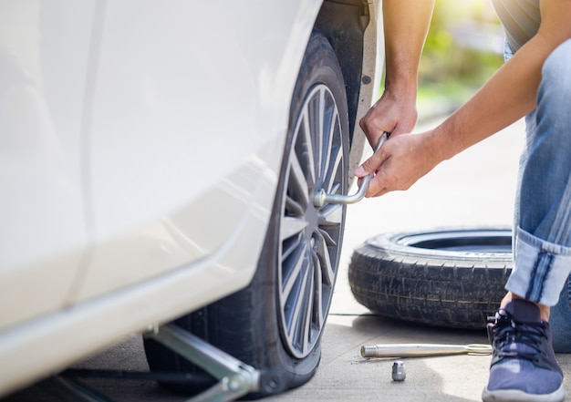 Man changing car tire with wheel wrench on street, technician fixing tire with wrench, repairing and maintenance concepts