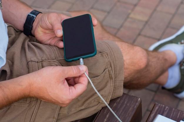 남자는 손에 전원 은행을 들고 스마트폰을 충전합니다. 가제트 충전용 휴대용 충전기.
