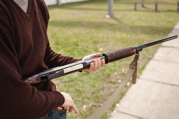 Man charges a pump action shotgun close up