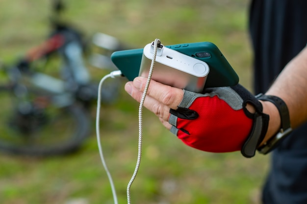 Man charges a smartphone with a power bank on the background of a bicycle in the forest.