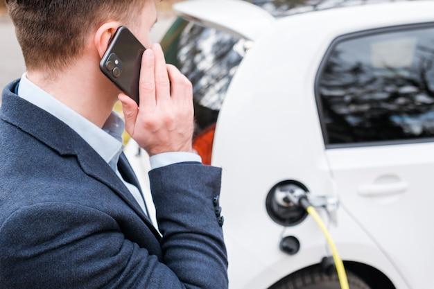 Человек заряжает электромобиль и разговаривает по смартфону