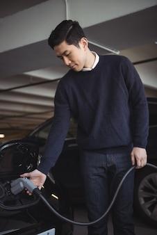 Человек заряжает автомобиль на станции зарядки электромобилей