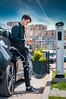Человек заряжает свой электромобиль на зарядной станции и использует смартфон