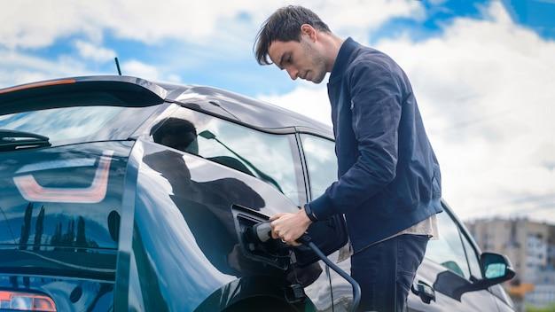 Человек заряжает свой электромобиль на зарядной станции