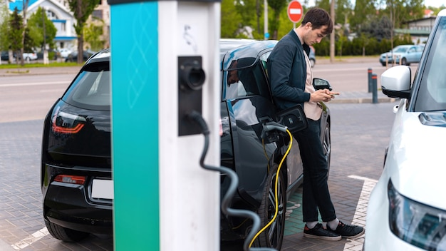 Man charging his electric car at charge station and using smartphone