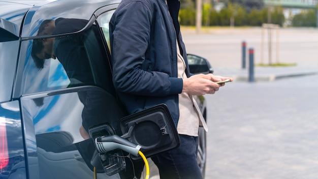 Uomo che carica la sua auto elettrica alla stazione di ricarica e utilizza lo smartphone