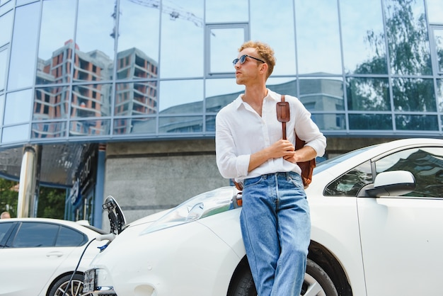Человек заряжает свой роскошный электромобиль на открытой станции перед современными новыми городскими зданиями