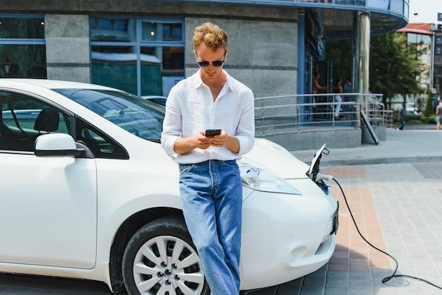 현대적인 새 도시 건물 앞 야외 스테이션에서 고급 전기 자동차를 충전하는 남자