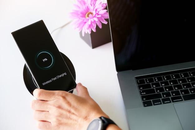Мужчина заряжает смартфон с помощью портативной беспроводной быстрой зарядки дома
