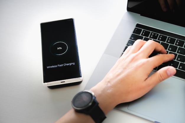 Человек зарядки смартфона с помощью портативной беспроводной быстрой зарядки на работе