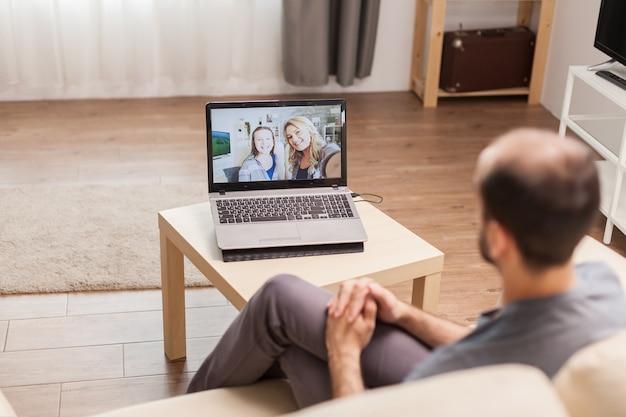 전 세계적으로 유행하는 전염병이 발생했을 때 화상 통화를 하는 동안 가족과 채팅하는 남자.