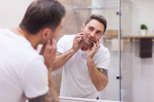 L'uomo controlla le condizioni della sua pelle nel riflesso dello specchio