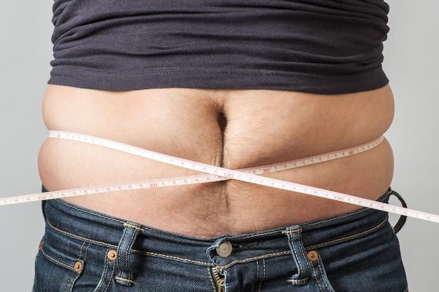 Человек проверить свой жир с помощью измерительной ленты