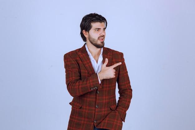 Uomo in giacca sportiva a quadri che punta a qualcosa a destra e ne parla.