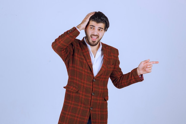Man in checked blazer pointing at something in the right and talking about it. Free Photo