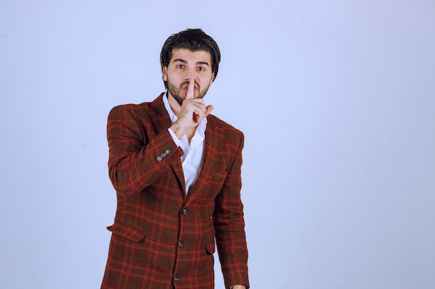 Uomo in giacca a quadri che chiede silenzio mostrando la sua bocca.