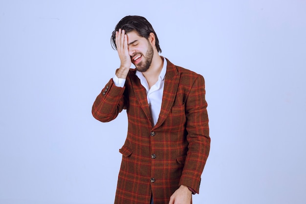 Man in checked jacket feeling very sad about something and crying.