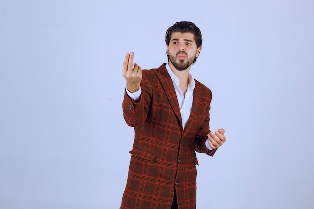 Man in checked jacket making a hand sign meaning a little amount.