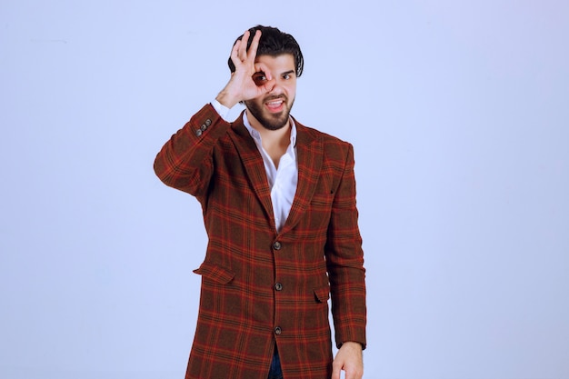 Man in checked jacket making ok sign.