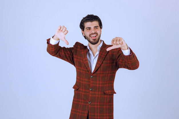 Man in checked jacket making thumb down.