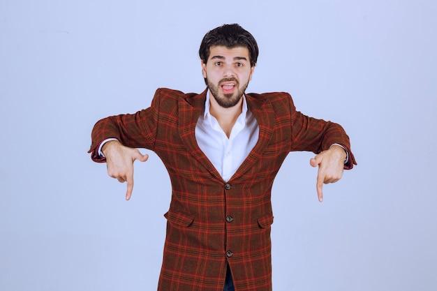 Uomo in giacca a quadri rivolto verso il basso con il dito e mostrando qualcosa.