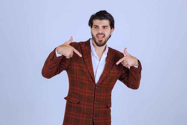 Uomo in giacca a quadri che indica se stesso e si esibisce.