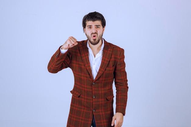 Uomo in giacca a quadri che mostra il suo pugno.