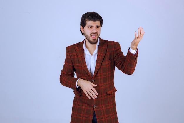 Uomo in giacca a quadri parlando di qualcosa con aggressività.