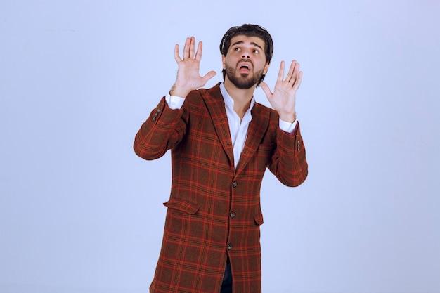 Uomo in giacca a quadri che cerca di fermare o rifiutare qualcosa.