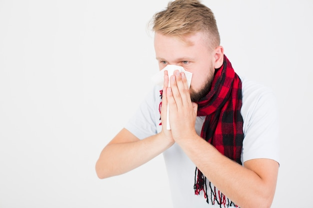 Man in checkered scarf blowing nose