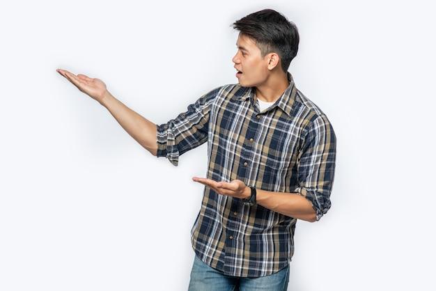 Uomo in una camicia a scacchi che punta le mani di lato