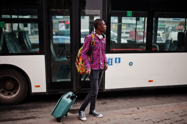Man in checkered shirt, with suitcase and backpack