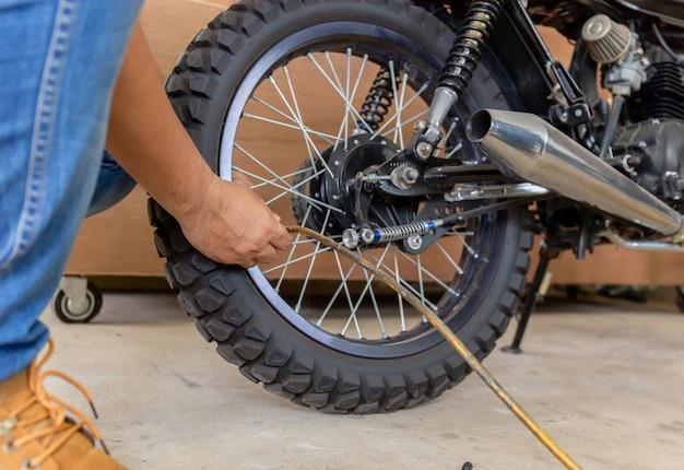 男は空気圧をチェックし、オートバイのタイヤの空気を充填