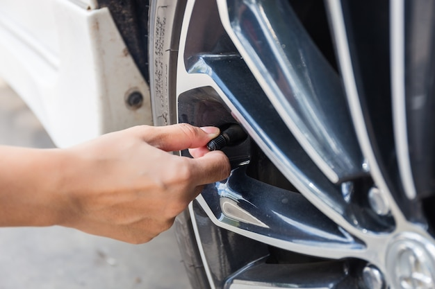 Man checking air pressure and filling air in the tires of car. concept picture