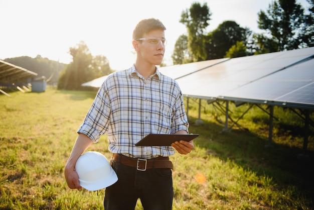 Человек проверяет и стоит возле солнечных батарей