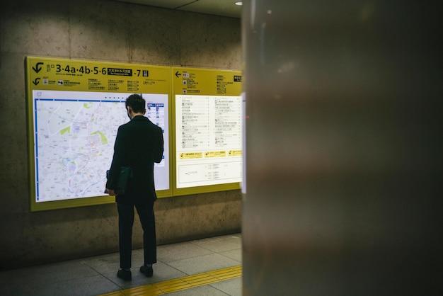 Человек проверяет доску объявлений на станции
