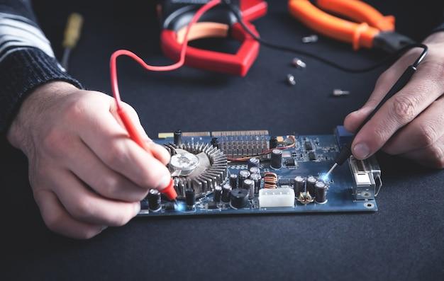 Человек проверяет материнскую плату компьютера с помощью мультиметра.