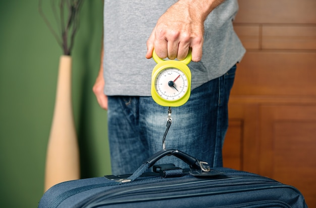 Мужчина проверяет вес ручной клади с помощью безынерционных весов по ограничениям бюджетных авиакомпаний