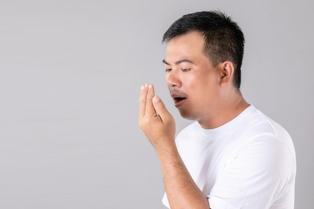 Man checking his breath with hand