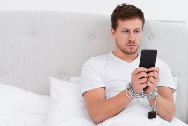 Man checking his phone after waking up