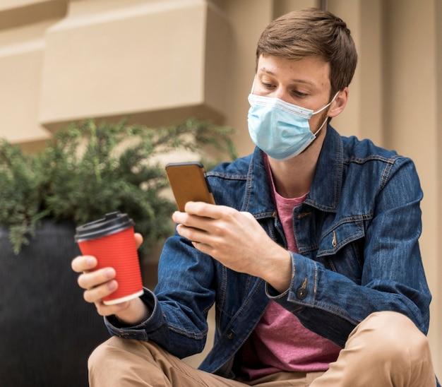 フェイスマスクをつけたまま屋外で携帯電話をチェックしている男性