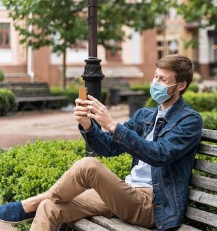 コピースペース付きのフェイスマスクを着用して携帯電話をチェックする男